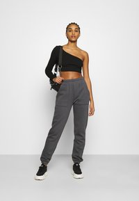 Nly by Nelly - COZY POCKET PANTS - Tracksuit bottoms - off-black - 1