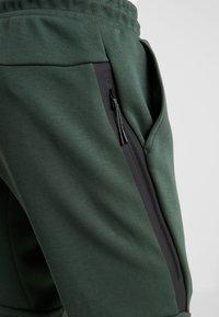 Nike Sportswear - Spodnie treningowe - galactic jade/black - 5