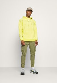 Karl Kani - SIGNATURE WASHED HOODIE UNISEX - Sweatshirt - light yellow - 1