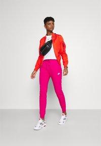 Nike Sportswear - Tracksuit bottoms - fireberry/white - 1