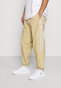 adidas Originals - LOCK UP UNISEX - Verryttelyhousut - beige tone - 0