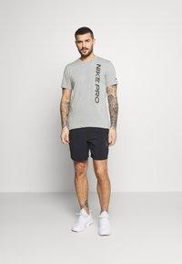 Nike Performance - BURNOUT - T-shirt z nadrukiem - particle grey/black - 1