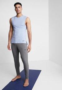 Nike Performance - M NK DRY PANT HPR DRY LT YOGA - Tracksuit bottoms - black - 1