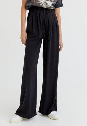 RUSTIKALE - Trousers - black