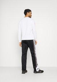 Champion - STRAIGHT HEM PANTS - Tracksuit bottoms - black - 2