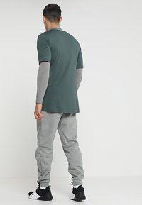 Nike Performance - THRMA TAPER - Pantalon de survêtement - dark grey heather/black - 2