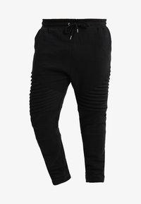 PLEAT - Tracksuit bottoms - black
