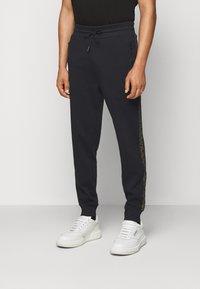 HUGO - DOKUMI  - Teplákové kalhoty - black/gold - 0