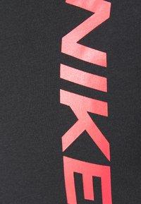 Nike Performance - BURNOUT - Print T-shirt - black/bright crimson - 5