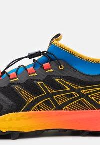 ASICS - FUJITRABUCO PRO - Trail running shoes - black/saffron - 5