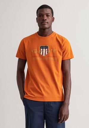 ARCHIVE SHIELD - Print T-shirt - savannah orange