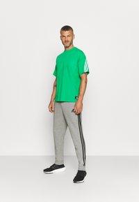 adidas Performance - Tracksuit bottoms - medium grey heather/black - 1