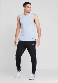 Nike Performance - DRY TAPERED PANT - Tracksuit bottoms - schwarz - 1