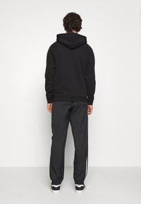 adidas Originals - ADICOLOR 3D TREFOIL 3-STRIPES TRACK PANTS - Tracksuit bottoms - black - 2