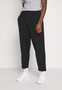 adidas Originals - WARMUP - Tracksuit bottoms - black - 0