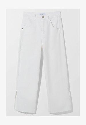 MIT SCHLITZEN AM SAUM - Flared Jeans - white
