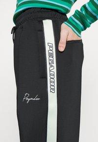 Pegador - WIDE TRACKPANTS UNISEX - Pantalon de survêtement - black/mint - 6