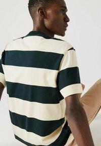 Lacoste - T-shirt imprimé - dunkelgrün / beige - 1