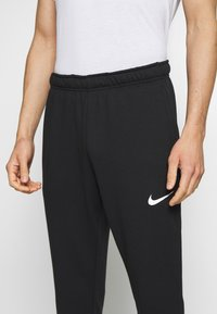 Nike Performance - DRY PANT TAPER - Tracksuit bottoms - black/white - 4