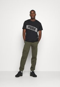 Puma - TRAIN GRAPHIC SHORT SLEEVE TEE - Print T-shirt - black/white - 1