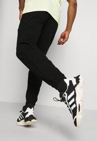 adidas Originals - COLLEGIATE CREST UNISEX - Tracksuit bottoms - black - 3