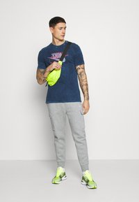 Nike Sportswear - CLUB PANT  - Pantalon de survêtement - grey heather/matte silver/white