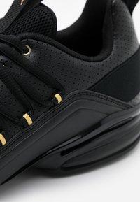 Puma - AXELION - Obuwie treningowe - black/team gold - 5