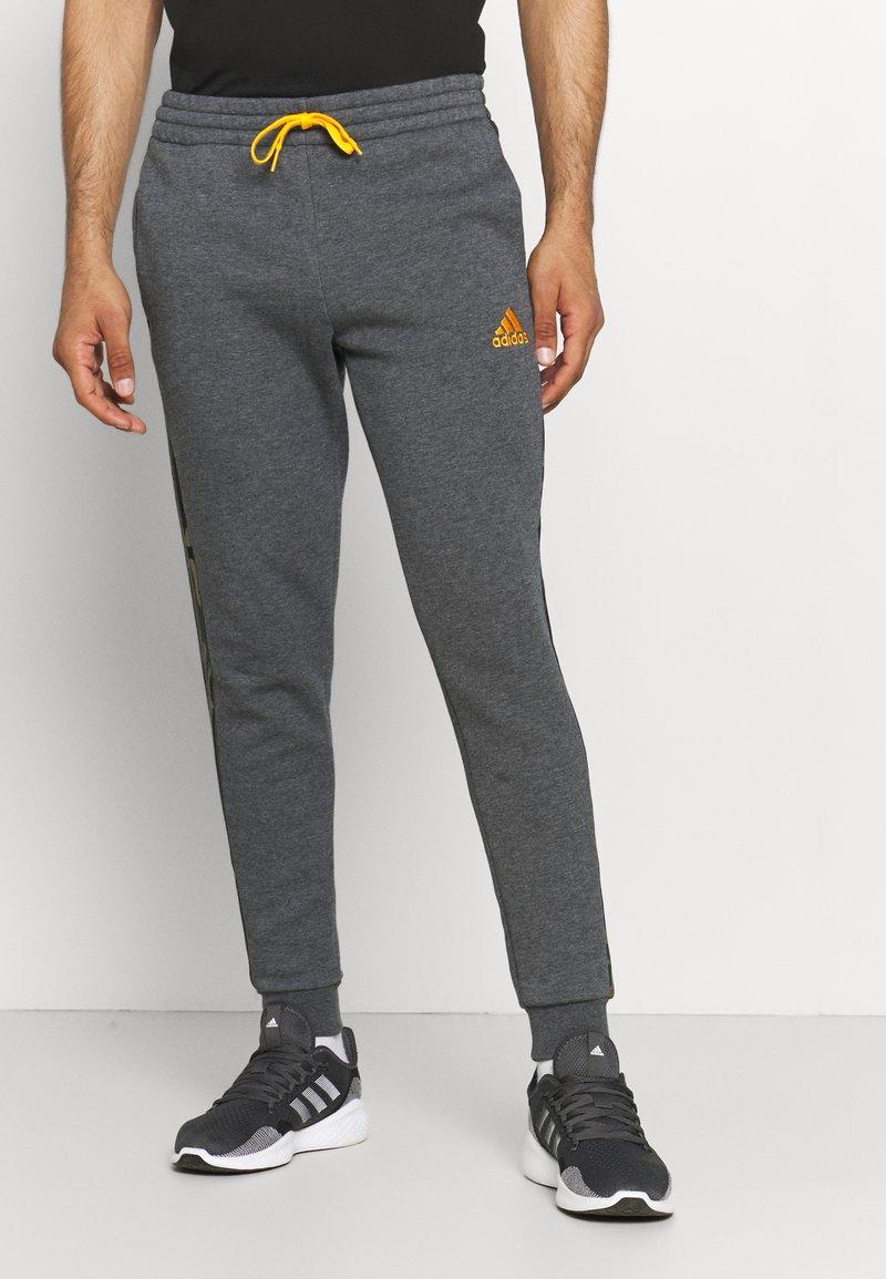 adidas Performance - CAMO - Tracksuit bottoms - dark grey heather/semi solar gold