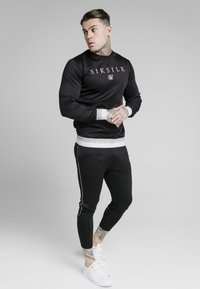 SIKSILK - DELUXE AGILITY JOGGER - Tracksuit bottoms - black - 1
