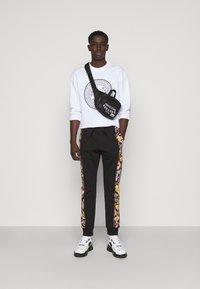 Versace Jeans Couture - HEAVY PRINT VERSAILLES - Tracksuit bottoms - black - 1