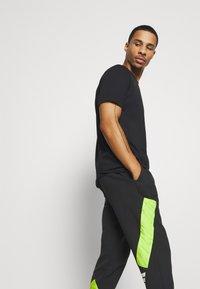 adidas Performance - URBAN PANT - Tracksuit bottoms - black/neon green - 3