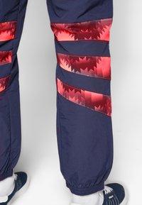 adidas Originals - FOOTBALL GRAPHIC TRACK PANTS - Tracksuit bottoms - blue - 3