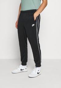 Nike Sportswear - REPEAT - Tracksuit bottoms - black - 0