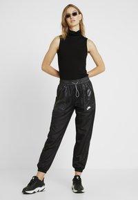 Nike Sportswear - PANT CARGO REBEL - Pantalon de survêtement - black/white - 1
