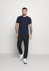 Lacoste Sport - TENNIS PANT TAPERED - Träningsbyxor - black/white - 1