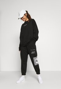 Missguided Petite - GRAPHIC - Tracksuit bottoms - black - 1