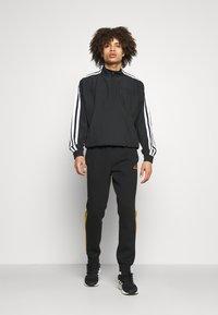 adidas Performance - 3 STRIPES  ESSENTIALS - Tracksuit bottoms - black/semi solar gold - 1