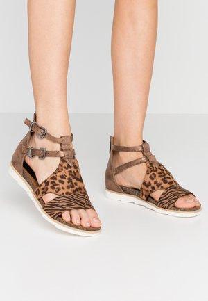 Sandaalit nilkkaremmillä - bronce