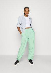 NA-KD - NA-KD X ZALANDO EXCLUSIVE - SPORTY FABRIC PANTS - Tracksuit bottoms - fresh mint - 1