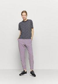 Under Armour - GRAPHIC PANTS - Pantalones deportivos - slate purple - 1