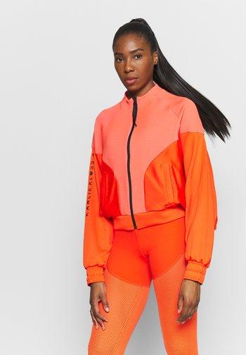 COVER UP - Training jacket - active orange/black