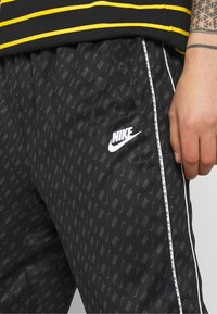 Nike Sportswear - REPEAT - Tracksuit bottoms - black/white - 4