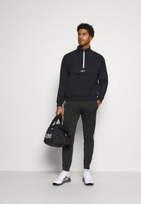 Reebok - VECTOR TRACK PANT - Pantalon de survêtement - black - 1