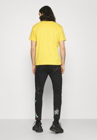 The Couture Club - NEON GRAFITTI CARROT FIT JEANS - Jeans slim fit - washed black - 2