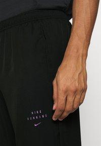 Nike Performance - Tracksuit bottoms - black - 5