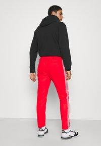 adidas Originals - BECKENBAUER UNISEX - Tracksuit bottoms - red - 2