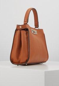Guess - UPTOWN CHIC TURNLOCK SATCHEL - Handbag - cognac - 3