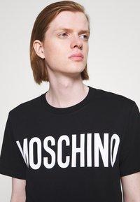 MOSCHINO - Print T-shirt - black - 8