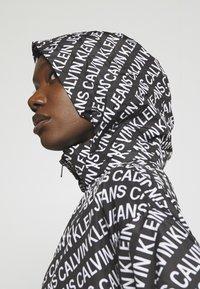 Calvin Klein Jeans - PACKABLE HOOD WINDBREAKER - Summer jacket - black - 5