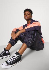 Nike Sportswear - Tracksuit bottoms - dark raisin/bright mango - 3